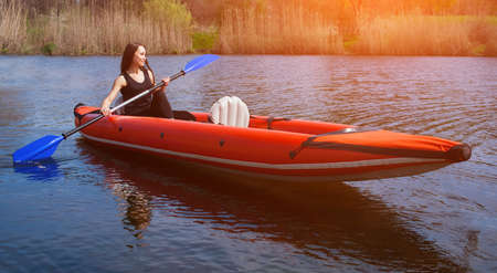 black white kayak: The smiling girl -the sportswoman with long,dark hair in black,sportswear rows with an oar on the lake in a red, inflatable canoe in a warm,summer,sunny day. Occupation by sports rowing on a kayaking. Stock Photo