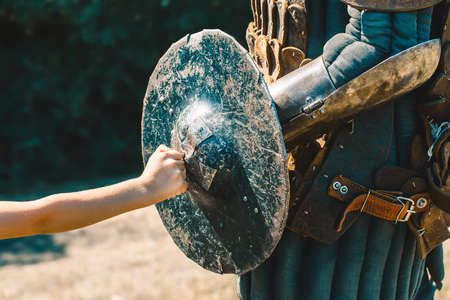 bruised: Little boy rests his fist on the knight, bruised, cracked, worn shield