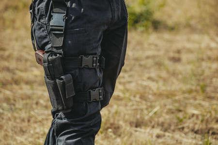 Het pistool verborgen in een holster hangen op het been van een soldaat.