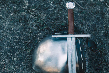 Knights helmet and shiny metal lying on the ground, it put an old steel sword with leather handle.