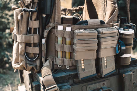 Army vest with a walkie-talkie, charged collars, stun grenades, luminous sticks, standing on a wooden box of ammunition. Stock Photo