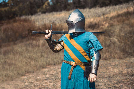 rivets: The knight in armor standing holding a sword in hand. Stock Photo