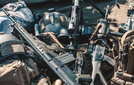 arsenal: automatic machine, machine gun, helmet, body armor piled in a heap lie on the ground. Stock Photo