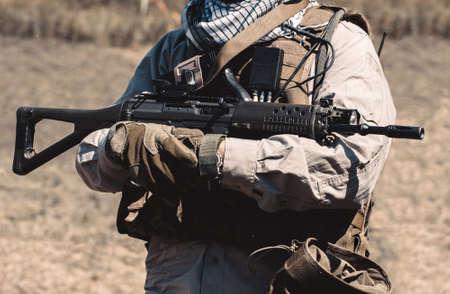 assault rifle: A soldier wearing a vest holding an assault rifle.