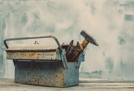 discolored: In the old, iron box are tools, used, rusty, discolored, metal, dirty wrenches of various sizes, chisel,bolt,pliers,hammer,chain,adjustable wrench,scissors.