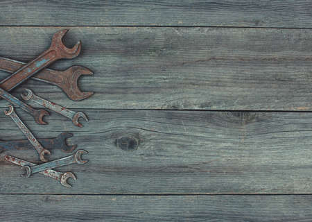 discolored: In the old, wooden, cracked, the working surface in the workshop lie in the left corner of the vintage, used, rusty, discolored, steel, metal, dirty wrenches of different sizes. Stock Photo