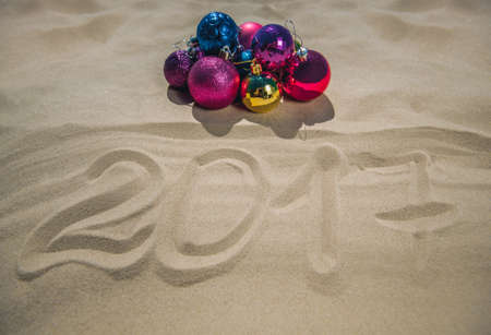 next year: Christmas colored balls lie on the beach, next to the sand, the date is written. New Year celebrations in the ocean or sea. Stock Photo