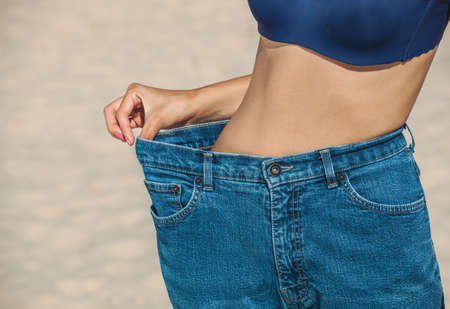 reducing: A young girl wears jeans that become large after weight loss and diet. Reducing excess weight. Healthy lifestyle. Stock Photo
