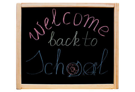 The inscription welcome back to school written with colorful chalk on a school, black board in a wooden frame on an isolated, white background.