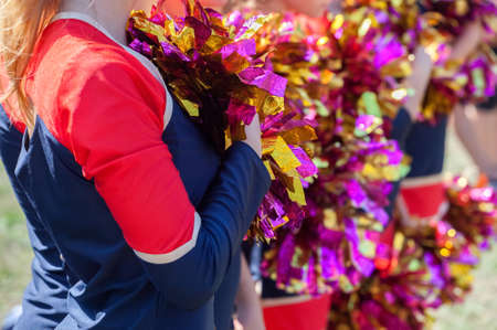 pom: Cheerleaders holding pom-poms in their hands.