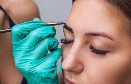 Cosmetolog- makeup-artiest past verfhaan op voorheen geplooide, ontwerp, afgewerkte wenkbrauwen in een schoonheidssalon in de sessiecorrectie. Professionele zorg voor gezicht.