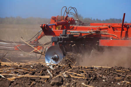 Large tractor pulling a plow and plow the field, remove the remnants of the previously beveled sunflower. The work of agricultural machinery. Stock Photo