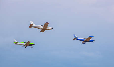 Three small aircraft flying in the sky against a background of clouds next to each other. Stock Photo