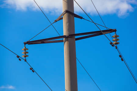 against the current: Intermediate, transmission line costs against the sky close-up on a clear, sunny day. power transmission by means of electric current.