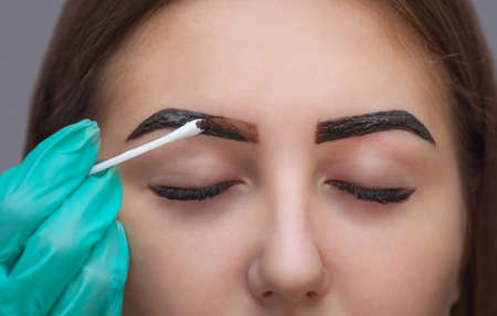 Master corrects makeup, it gives shape and color the eyebrows henna in a beauty salon, Spa. Professional skin care. Imagens