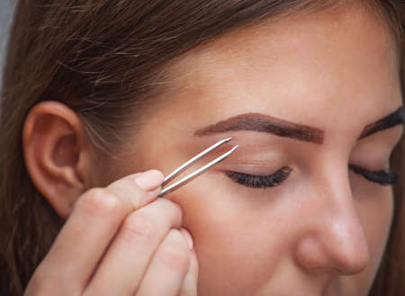 Master makeup corrects, and gives shape to pull out with forceps previously painted with henna eyebrows in a beauty salon. Professional care for face