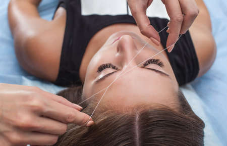 Master corrects makeup, gives shape and thread plucks eyebrows in a beauty salon. Professional care for face. Stock Photo