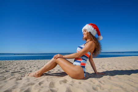 Young, attractive girl in a black bathing suit and hat of Santa Claus sitting on the beach, by the sea. The concept of the New Year and Christmas holidays.