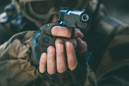 the soldier in the performance of tasks in camouflage and protective gloves holding a pistol with the hammer cocked takes aim for shot. War Zone. 写真素材