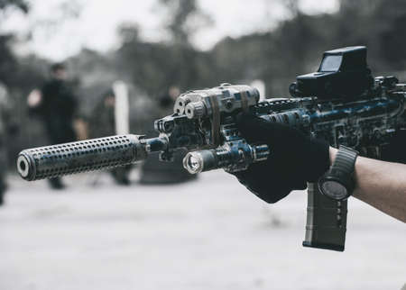 soldiers in missions in camouflage and protective gloves holding in hand with the hammer cocked machine takes aim for shot. War Zone.
