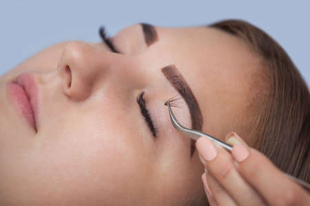 master volume: Makeup Master corrects, and strengthens eyelashes beams, holding out a pair of tweezers in a beauty salon. Professional care for the skin and eyes.