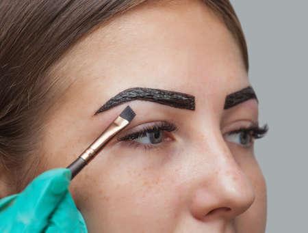 make-up artist van toepassing verf henna op eerder geplukt, ontwerp, bijgesneden wenkbrauwen in een schoonheidssalon in de sessie correctie. Professionele zorg voor het gezicht. Stockfoto