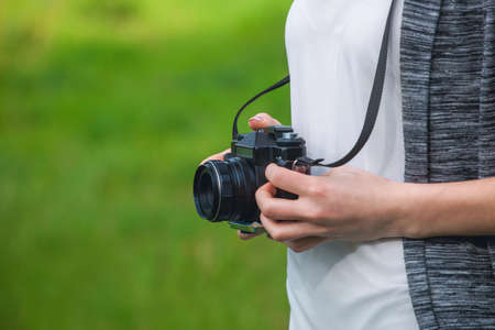 Beautiful girl-photographer with curly hair holds a camera and make a photo, spring outdoors in the park. The concept of tourism and travel. Stock Photo