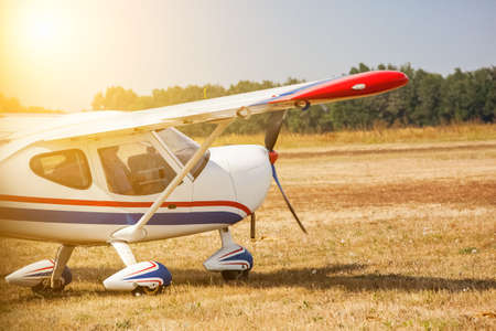 A small private plane with propeller stands at the airport, in a bright, sunny day. Stock Photo
