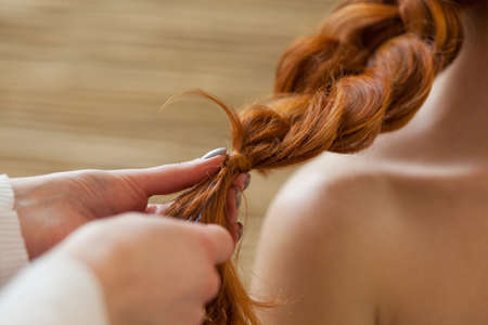 Beautiful, with long, red-haired hairy girl, hairdresser weaves a French braid close-up, in a beauty salon. Professional hair care and creating hairstyles.