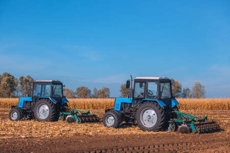 previously: Two big blue tractor plowing a field and remove the remains of previously mown corn. The work of agricultural machinery. Harvest