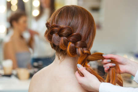 Beautiful red-haired hairy girl, hairdresser weaves a French braid, close-up in a beauty salon. Professional hair care and creating hairstyles.