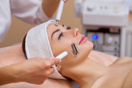 The physician-cosmetologist makes the apparatus a procedure of galvanic ultrasound cleaning of the face skin of a beautiful, young woman in a beauty salon. Cosmetology and professional skin care. Stock Photo