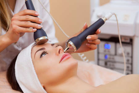 The doctor-cosmetologist makes the procedure an ultrasonic cleaning of the facial skin of a beautiful, young woman in a beauty salon.Cosmetology and professional skin care.