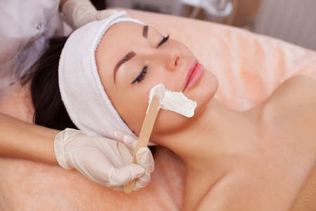 antiaging: The doctor is a cosmetologist for the procedure of cleansing and moisturizing the skin, applying a mask with stick to the face of a young woman in beauty salon.Cosmetology and professional skin care. Stock Photo
