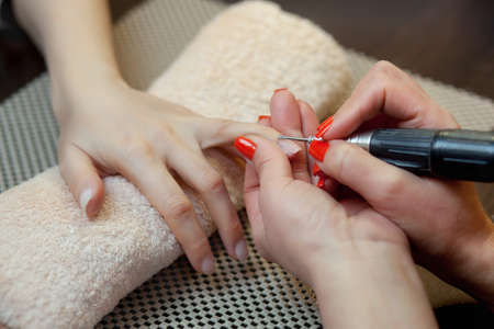 The master of the manicure saws and attaches a nail shape during the procedure of nail extensions with gel in the beauty salon. Professional care for hands.