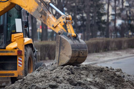 A large yellow excavator stands in the middle of the street near the dug hole. Reklamní fotografie