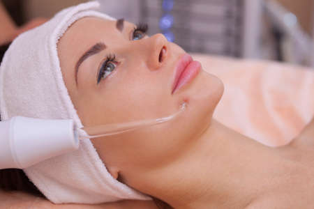 The doctor-cosmetologist makes the procedure Microcurrent therapy of the facial skin of a beautiful, young woman in a beauty salon.Cosmetology and professional skin care.