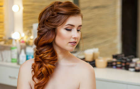 Beautiful girl, with long, red-haired hairy. Hairdresser weaves a French braid, close-up in a beauty salon. Professional hair care and creating hairstyles. Stock Photo