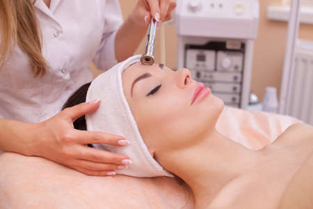 The doctor-cosmetologist makes the procedure Microdermabrasion of the facial skin of a beautiful, young woman in a beauty salon.Cosmetology and professional skin care. Stock Photo