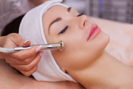 Die Arzt-Kosmetikerin macht die Prozedur Microdermabrasion der Gesichtshaut einer schönen, jungen Frau in einem Beauty-Salon.Kosmetologie und professionelle Hautpflege. Standard-Bild