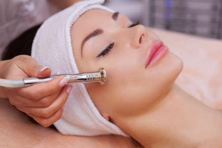 Le médecin-cosmétologue fait la procédure Microdermabrasion de la peau du visage d'une belle jeune femme dans un salon de beauté. Cosmétologie et soins de la peau professionnelle. Banque d'images