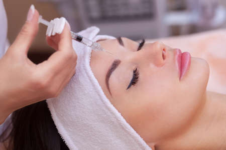 The doctor cosmetologist makes the Botulinotoxin injection procedure for tightening and smoothing wrinkles on the face skin of a beautiful, young woman in a beauty salon.Cosmetology skin care.