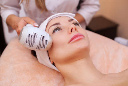 The doctor-cosmetologist makes the procedure Cryotherapy of the facial skin of a beautiful, young woman in a beauty salon.Cosmetology and professional skin care. Stock Photo