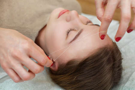 Master corrects makeup gives shape and thread plucks eyebrows in a beauty salon. Professional care for face. Stock Photo