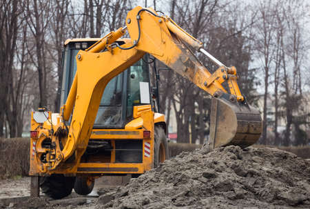 A large yellow excavator stands in the middle of the street near the dug hole. Stock Photo