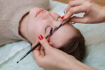 The make-up artist combs and shear her brows with scissors to a beautiful young girl in a beauty salon. Professional care for face. Stock Photo
