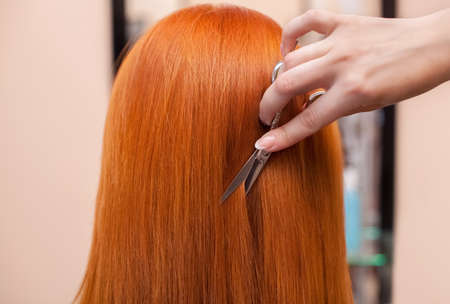 De kapper doet een kapsel met een schaar van haar aan een jong meisje met rood haar in een schoonheidssalon.