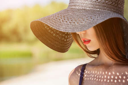 Attractive girl in a black hat worn on the head, on the beach. Close up of the face can be seen. Stock Photo