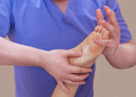 orthopedist: The doctor-podiatrist does an examination and massage of the patients foot in the clinic. Stock Photo