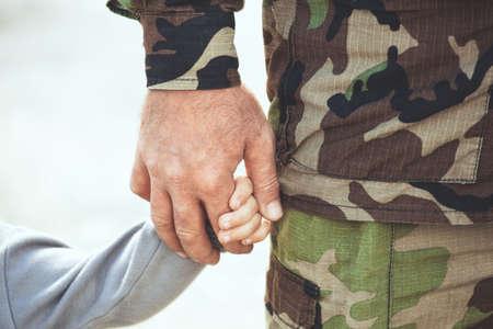 Twee handen van één familie - vader en kind samen. Het concept van gezinseenheidsbescherming ondersteunt welvaartsliefde en ouderlijk geluk.